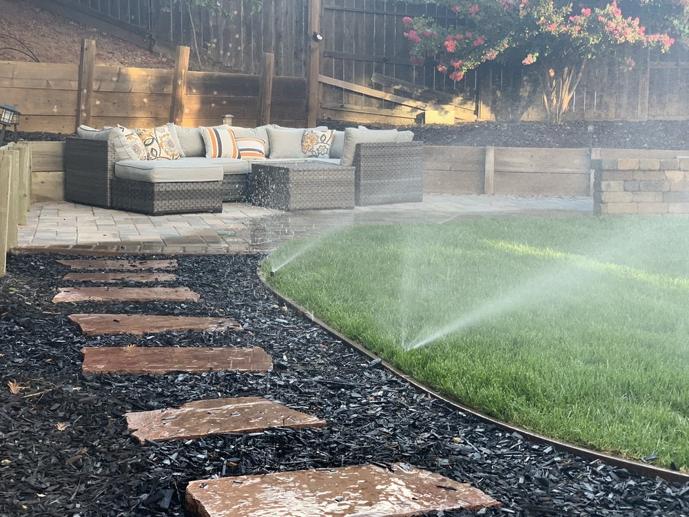 paver patio seating area with black mulch, walkway, lawn, and running sprinklers