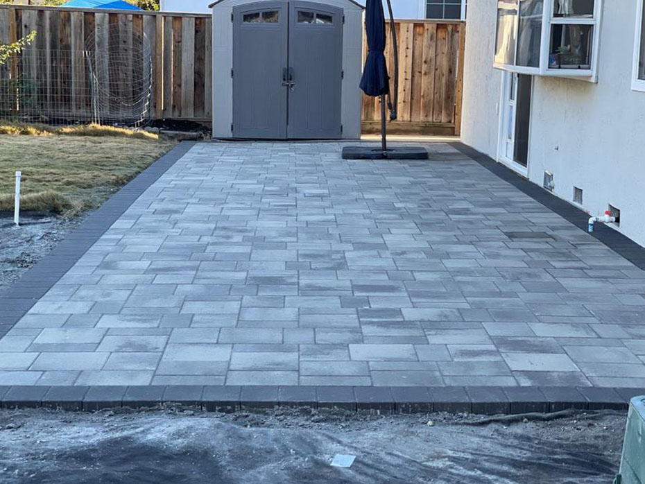 Grey paver patio installed in Hayward with a shed